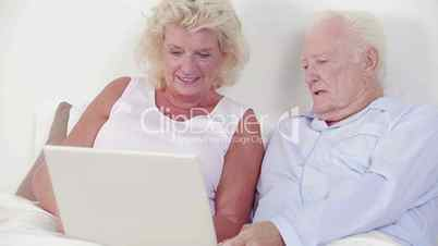 Old couple using a laptop and speaking