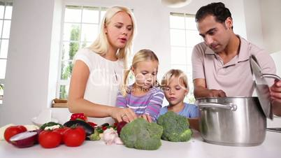 Posing family putting vegetables in a pot