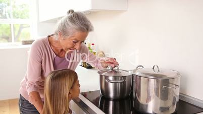 Girl happily cooking with her grandmother