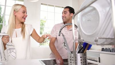 Joyful couple washing dishes together