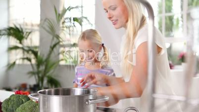 Mother and her daughter putting vegetables in a pan