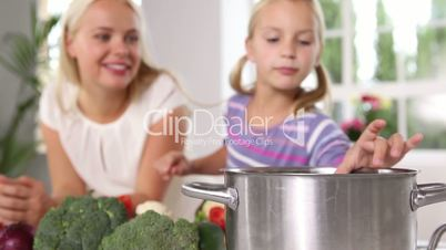 Mother and daughter putting vegetables in a pan