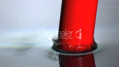 Red cylinder dropping in water