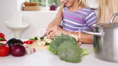 Focused mother teaching cutting vegetables