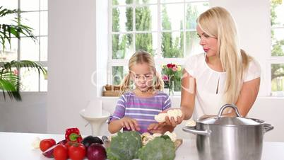 Mother and her daughter juggling with vegetables