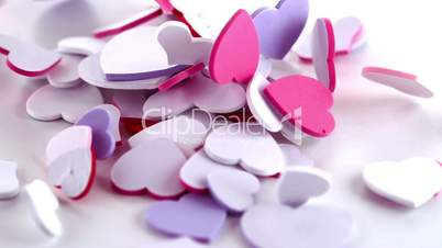 Many pink heart confetti dropping on the floor