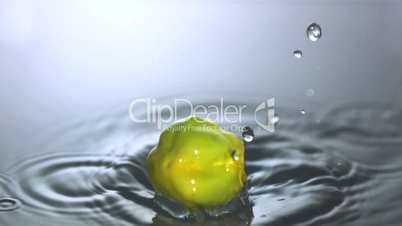 Green chili falling in water close up