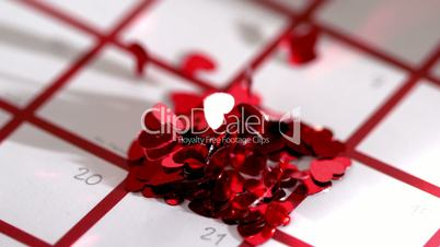Heart confetti scattering on calendar