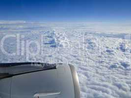 Cloudscape and engine seen through an airplane window