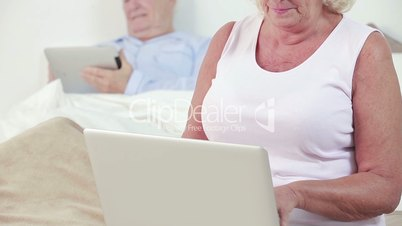 Old couple using a laptop and tablet