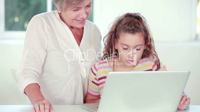 Child learning to use laptop with grandmother