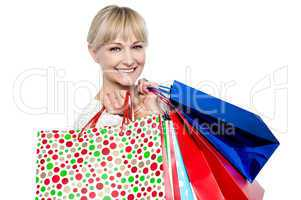 Pretty female carrying shopping bags over shoulders