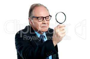 Detective  exploring through a magnifying glass
