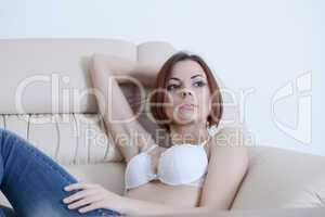 Pretty girl in bra and jeans sit on sofa