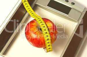 Personenwaage mit Apfel und Maßband