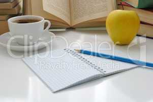 notebook with a pencil on a table with a cup of coffee and an ap