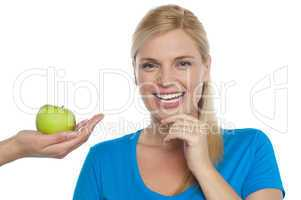 Attractive woman is being offered a green apple