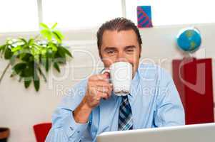 Smiling male manager enjoying hot coffee
