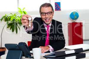 Happy male executive handing over the keys