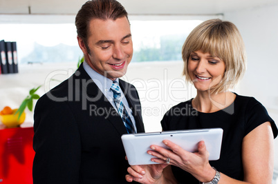 Female secretary showing appointments to boss saved on tablet device