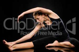 Young woman in separate leg stretching pose
