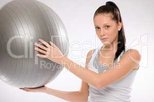 Woman holding fitness ball on white background