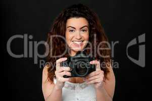 Cheerful woman holding newly launched camera