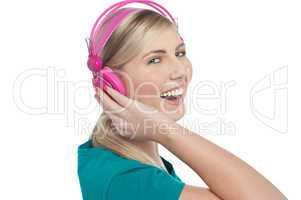 Joyous blonde teen listening to lively music