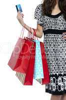 Stylish woman walking with shopping bags and credit card