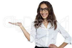 Joyous woman in spectacles posing with open palm