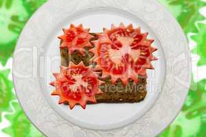 Tomato gear wheels on black bread
