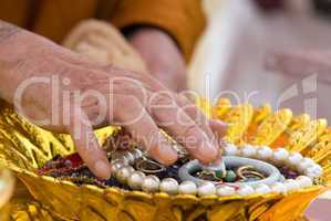 Hand of Buddhist monk painting religious symbols on amulets with his finger. Shallow depth of field.