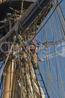 Tall ship crew putting away sails