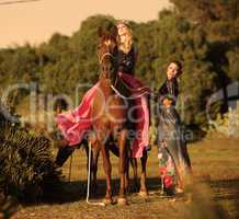 two woman riding horse