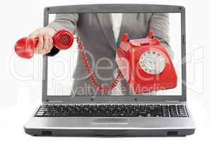 Businesswoman reaching out from laptop handing phone receiver