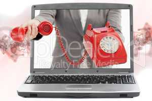 Woman reaching out from laptop handing phone receiver