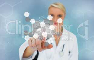 Blonde doctor pressing touchscreen displaying chemical formula
