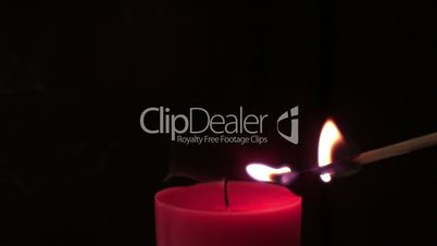 Pink candle lit by match