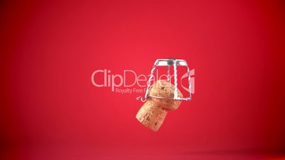 Champagne cork dropping and seperating on red background