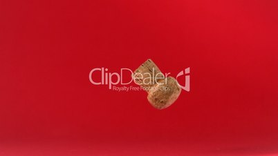 Champagne cork dropping and boucing on red background