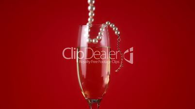Pearl necklace falling into champagne flute