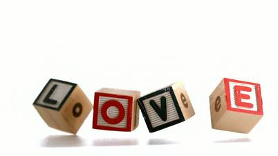 Building blocks spelling out love falling and bouncing
