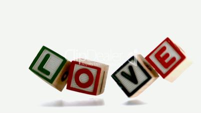 Wooden blocks spelling out love falling