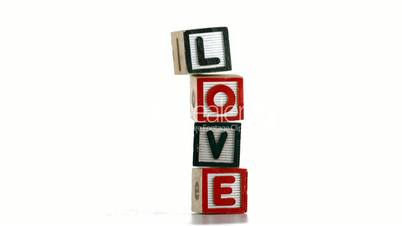 Stacked building blocks spelling out love falling over