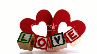 Building blocks spelling out love falling with heart ornament