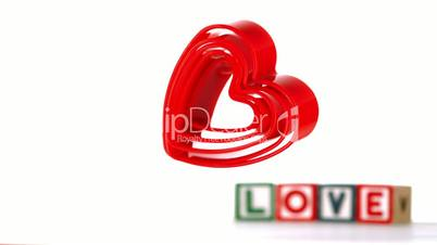 Heart ornaments falling with blocks spelling love in background