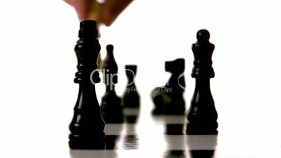 White chess piece knocking over many black pieces