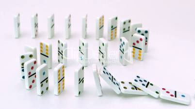 White dominoes falling over