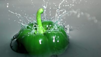 Green bell pepper falling into water