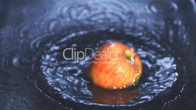 Red apple falling into water